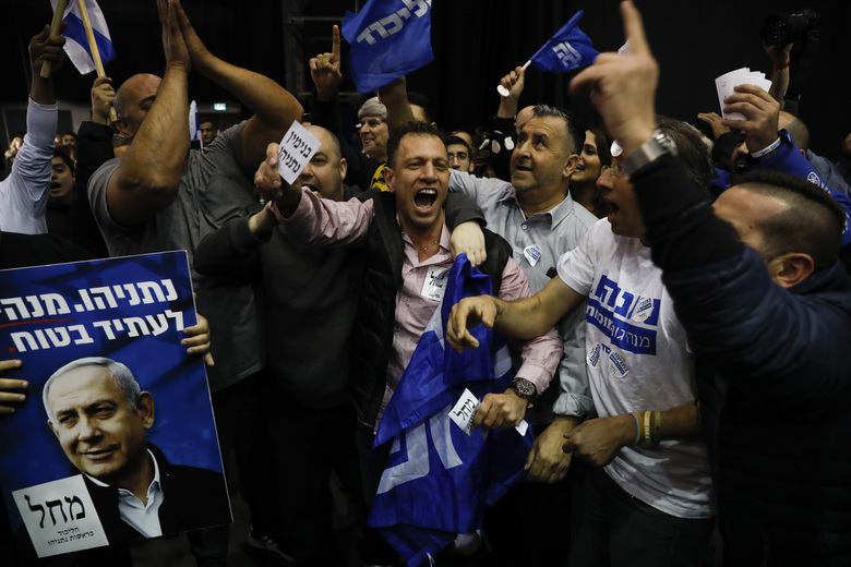 Israeli Prime Minister Benjamin Netanyahu's supporters celebrate first exit poll results for the Israeli elections at his party's headquarters in Tel Aviv, Israel, Monday, March 2, 2020. (AP Photo/Ariel Schalit)