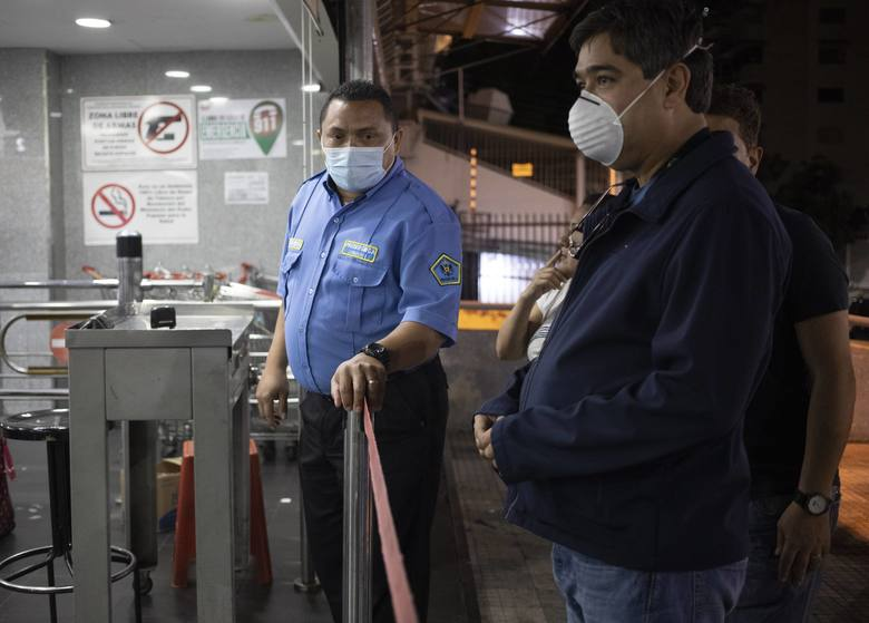 A costumer waits to enter a supermarket in Caracas, Venezuela, after Venezuelan President Nicolás Maduro today has ordered residents in the capital of Caracas and six states to stay home under a quarantine bid to control the spread of the coronavirus on Sunday, March, 15, 2020. (AP Photo/Ariana Cubillos)