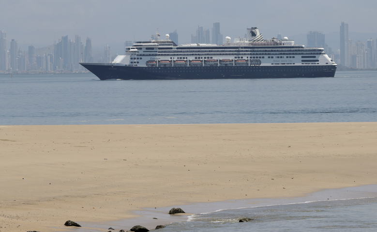 The Zaandam cruise ship, carrying dozens of guests with flu-like symptoms, arrives to the bay of Panama City, seen from Isla de Taboga, Panama, Friday, March 27, 2020, amid the worldwide spread of the new coronavirus. Once the vessel reaches Panamanian waters, health authorities are expected to board the ship to test passengers and decide whether it can cross the Panama Canal to head on towards Fort Lauderdale. (AP Photo/Arnulfo Franco)