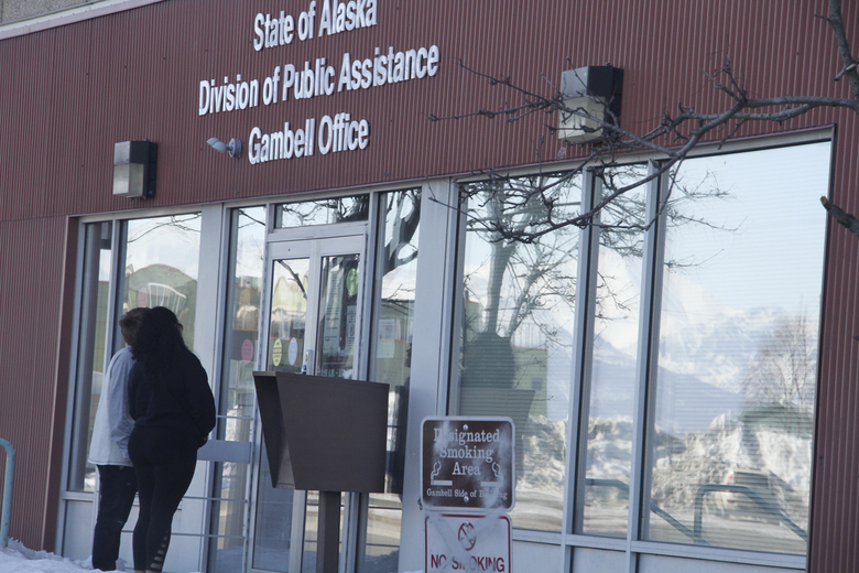Two people attempt to get inside the State of Alaska Division of Public Assistance office near downtown Anchorage, Alaska, on Monday, March 30, 2020.   State health officials say a 73-year-old Anchorage resident was the latest fatality from COVID-19.. The individual was tested and admitted to an Anchorage hospital March 23 and died Saturday. (AP Photo/Mark Thiessen)