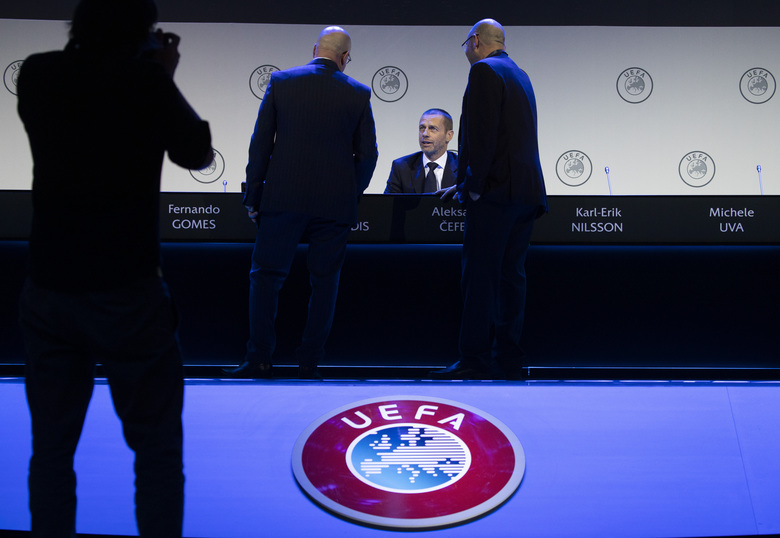 Delegates talk to UEFA President Aleskander Ceferin, center, during a meeting of European soccer leaders at the congress of the UEFA governing body in Amsterdam's Beurs van Berlage, Netherlands, Tuesday, March 3, 2020. (AP Photo/Peter Dejong)