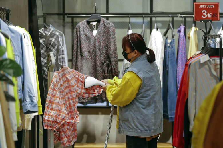 In this photo released by Xinhua News Agency, a worker wearing a protective face mask irons clothes at a re-opened shopping mall in in Wuhan in central China's Hubei province, Monday, March 30, 2020. Shopkeepers in the city at the center of China's virus outbreak were reopening Monday but customers were scarce after authorities lifted more of the anti-virus controls that kept tens of millions of people at home for two months. (Shen Bohan/Xinhua via AP)