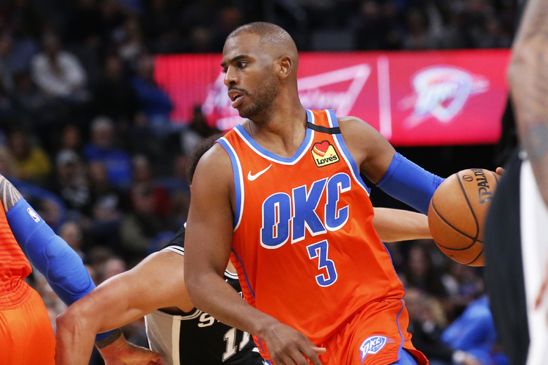 Oklahoma City Thunder guard Chris Paul (3) drives around San Antonio Spurs guard Bryn Forbes, rear, in the second half of an NBA basketball game Sunday, Feb. 23, 2020, in Oklahoma City. (AP Photo/Sue Ogrocki)