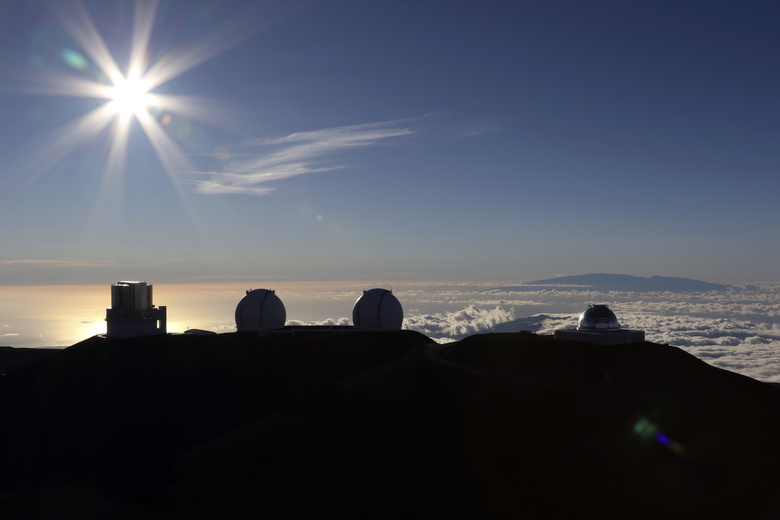 "FILE – In this July 14, 2019, file photo, the sun sets behind telescopes at the summit of Mauna Kea in Hawaii. The cost to build a giant telescope that's unpopular among many Native Hawaiians is now estimated to have ballooned by a billion dollars. ""While an exact updated project cost will depend on when and where on-site construction begins for the Thirty Meter Telescope, the latest estimate for the TMT project is in the range of $2.4 billion in 2020 dollars,"" Gordon Squires, TMT vice president, said in a statement this week. Construction of one of the world's largest telescopes on Hawaii's tallest mountain, Mauna Kea, has been stalled by foes of the embattled project who say the telescope will desecrate land held sacred to some Native Hawaiians. (AP Photo/Caleb Jones, File)"
