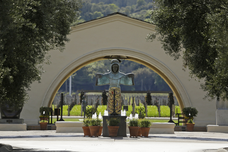 In this photo taken Thursday, March 19, 2020, a sculpture of St. Francis of Assisi, created by Beniamino Bufano, looks out over the empty entryway to the Robert Mondavi Winery in Oakville, Calif. Wineries in the Napa Valley are closed due to coronavirus restrictions expect for production, but some allow customers to pick up shipments of wine and for direct purchases. (AP Photo/Eric Risberg)