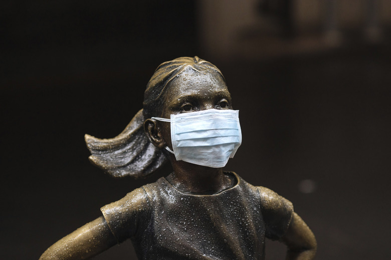 "A surgical mask is placed on The ""Fearless Girl"" statue outside the New York Stock Exchange on Thursday, March 19, 2020, in New York. Stocks are swinging between gains and losses in early trading on Wall Street Thursday, but the moves are more subdued than the wild jabs that have dominated recent weeks.    (AP Photo/Kevin Hagen)"