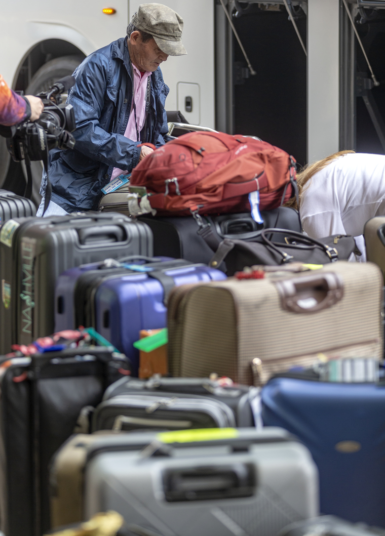 People arrive at the San Antonio International Airport Tuesday, March 3, 2020 after being released from quarantine at JBSA-Lackland. The people were evacuated from the coronavirus-infected Diamond Princess cruise ship in Japan and had been held in quarantine at Lackland to ensure they were not infected with the virus.  (William Luther/The San Antonio Express-News via AP)