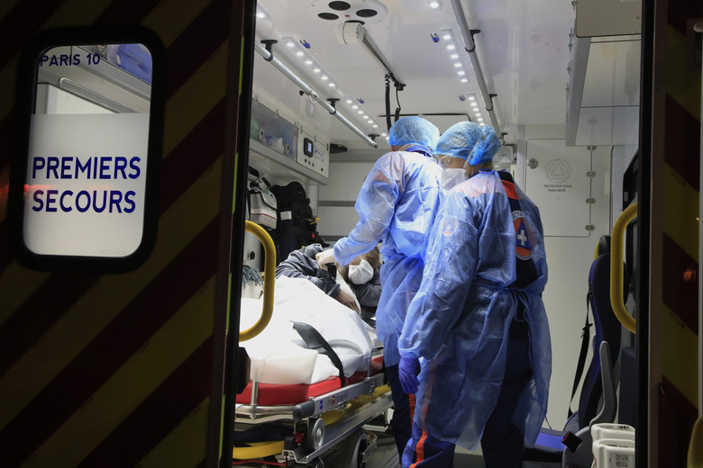 In this photo taken Thursday, March 26, 2020, members of the Civil Protection service, Vincent Jactel, left, and Aurore Lejeune, right, take care of a 27-year-old pregnant woman suspected of being infected with the Covid-19 virus in an ambulance in Paris. They don't have to put themselves in harm's way, but the volunteers of France's well-known Civil Protection service choose the front line in the fight against the coronavirus. (AP Photo/Michel Euler)