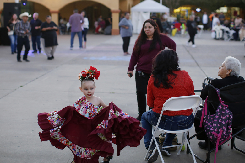 In this Feb. 8, 2020, photo, people gather during the celebration of the town's 45th year since it was incorporated, in Guadalupe, Ariz. Today, nearly a third of Guadalupe's 6,500 residents say they are Native American and about 75% of all races identify as Hispanic. Small, poor and largely Latino communities like these around the U.S. historically have been undercounted, an analysis by The Associated Press shows, posing challenges for Census workers in a tally that's supposed to ensure federal dollars get to communities needing them most. (AP Photo/Dario Lopez-MIlls)