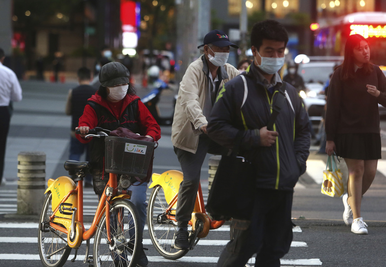 People wear face masks to protect against the spread of the coronavirus in Taipei, Taiwan, Tuesday, March 31, 2020. The new coronavirus causes mild or moderate symptoms for most people, but for some, especially older adults and people with existing health problems, it can cause more severe illness or death. (AP Photo/Chiang Ying-ying)