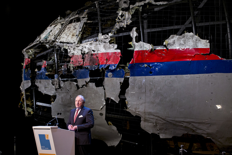 -FILE- In this Tuesday, Oct. 13, 2015, file image, with the reconstructed cockpit displayed behind, Tjibbe Joustra, head of the Dutch Safety Board presents the board's final report into what caused Malaysia Airlines Flight 17 to break up high over Eastern Ukraine last year, killing all 298 people on board, during a press conference in Gilze-Rijen, central Netherlands. United by grief across oceans and continents, families who lost loved ones when Malaysia Airlines Flight 17 was shot down in 2014 hope that a trial starting next week will finally deliver them something that has remained elusive ever since: The truth. (AP Photo/Peter Dejong, File)