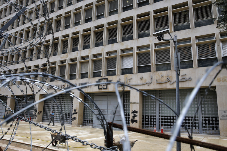 In this Wednesday, March 18, 2020 photo, a worker walks outside the Lebanese Central Bank that has been shut down as part of the preventive measures against the coronavirus, in Beirut, Lebanon. The COVID-19 pandemic has managed to do what various wars could not: Close bars, restaurants and entertainment spots across the tiny Mediterranean country. It's another economic gut punch, delivered at a time when Lebanon is mired in the worst financial crisis in its history — one that could hasten the country's long-feared economic collapse. (AP Photo/Bilal Hussein)