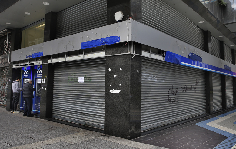 In this Wednesday, March 18, 2020 photo, people use an ATM outside a bank that has been shut down as part of the preventive measures against the coronavirus, in Beirut, Lebanon. COVID-19 has managed to do what various wars could not: Close bars, restaurants and entertainment spots across the tiny Mediterranean country. It's another economic gut punch, delivered at a time when Lebanon is mired in the worst financial crisis in its history — one that could hasten the country's long-feared economic collapse. (AP Photo/Bilal Hussein)