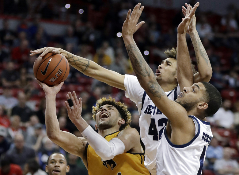 Wyoming's Hunter Maldonado shoots as Nevada's K.J. Hymes (42) and Robby Robinson (1) defend during the first half of a Mountain West Conference tournament NCAA college basketball game Thursday, March 5, 2020, in Las Vegas. (AP Photo/Isaac Brekken)