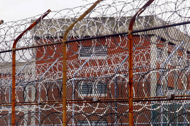 FILE – In this March 16, 2011, file photo, a security fence surrounds inmate housing on the Rikers Island correctional facility in New York. Health experts say prisons and jails are considered a potential epicenter for America's coronavirus pandemic. (AP Photo/Bebeto Matthews, File)