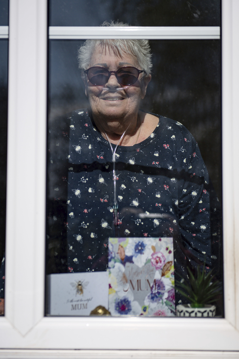 76-year old Olive Trotman, looks out from her home during as she is visited on Mother's Day by her son Mark, his wife Denise and his sister Kelly, in Napton, England, Sunday March 22, 2020. Olive suffers from a pulmonary disease and is taking the precaution of communicating at a safe distance or through a glass window, to limit the potential spread of COVID-19 coronavirus.  Sunday is Mother's Day in Britain and the government has a stark message for millions of citizens, that visiting your mom could kill her as for older adults and people with existing health problems, the virus can cause severe illness, including pneumonia. (Jacob King / PA via AP)