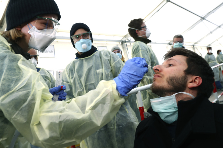 FILE – In this March 23, 2020, file photo, medical employees demonstrate testing, at a coronavirus test center for public service employees, during a media presentation in Munich, Germany. Labs were quick to ramp up their testing capacity and now experts say up to 500,000 tests can be conducted in Germany per week. That quick work, coupled with the country's large number of intensive care unit beds and its early implementation of social distancing measures, could be behind Germany's relatively low death toll.  (AP Photo/Matthias Schrader, File)
