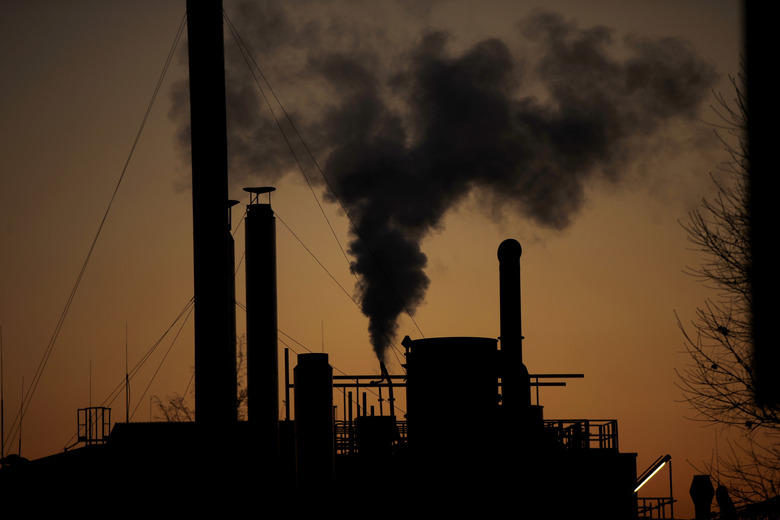 FILE – In this Friday, Dec. 14, 2018 filer, smoke billows from a chimney of a factory, in Ospiate, near Milan, Italy. The eurozone's third-largest economy and a major exporter, Italy on Wednesday becomes the first western industrialized nation to idle swaths of industrial production to stop the spread of coronavirus by keeping yet more of the population at home. The new coronavirus causes mild or moderate symptoms for most people, but for some, especially older adults and people with existing health problems, it can cause more severe illness or death. (AP Photo/Luca Bruno, File)