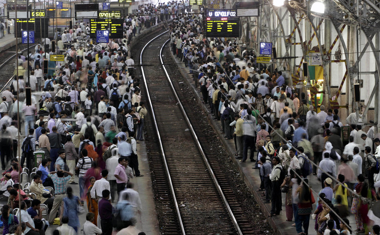 FILE – In this Wednesday, July 11, 2012, file photo, Indian commuters wait for trains at the Churchgate railway station in Mumbai, India. India's colossal passenger railway system has come to a halt Sunday, March 22, 2020, as officials take emergency measures to keep the coronavirus pandemic from spreading in the country of 1.3 billion. The railway system is often described as India's lifeline, transporting 23 million people across the vast subcontinent each day, some 8.4 billion passengers each year. (AP Photo/Rajanish Kakade, File)