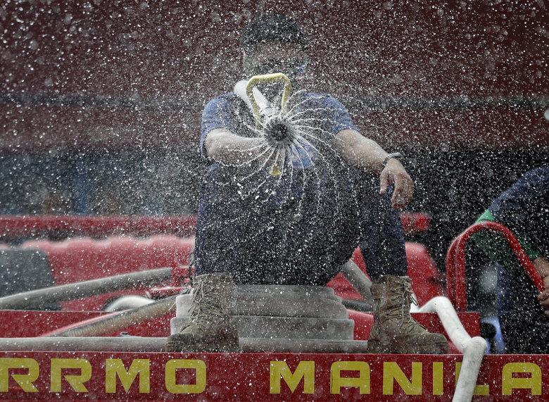 Firemen spray disinfectants outside a public market in Manila, Philippines, Wednesday, March 11, 2020. For most people, the new coronavirus causes only mild or moderate symptoms, such as fever and cough. For some, especially older adults and people with existing health problems, it can cause more severe illness, including pneumonia. (AP Photo/Aaron Favila)