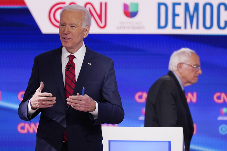 FILE – In this March 15, 2020, file photo Sen. Bernie Sanders, I-Vt., right, and former Vice President Joe Biden, left, return to the stage after a commercial break in a Democratic presidential primary debate at CNN Studios in Washington. White House contenders aren't typically bashful about asking for money. But as the coronavirus pandemic upends life, President Donald Trump and his likely Democratic rival, Biden, suddenly find themselves navigating perilous terrain. (AP Photo/Evan Vucci, File)
