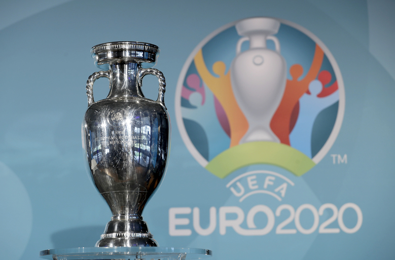 FILE – In this Thursday, Oct. 27, 2016 file photo the Euro soccer championships trophy is seen in front of the logo during the presentation of Munich's logo as one of the host cities of the Euro 2020 European soccer championships in Munich, Germany. UEFA, are set to make a final decision when the UEFA executive committee meets on Tuesday March 17, 2020 after talks with clubs and leagues, about possibly delaying the Euro 2020 soccer tournament by a year as the continent grapples with the outbreak of the coronavirus. (AP Photo/Matthias Schrader, File)