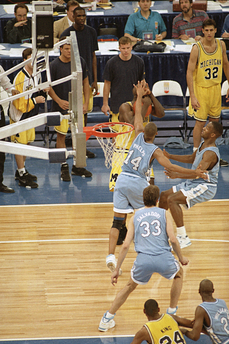 FILE – In this April 5, 1993 file photo, Michigan's Chris Webber, guarded by North Carolina's Derrick Phelps (14), calls a timeout in the closing moments of the NCAA Final Four championship game at the Superdome in New Orleans. Webber was called for a technical foul because they had no time outs left and North Carolina went on to win, 77-71. (AP Photo/Bill Haber, File)