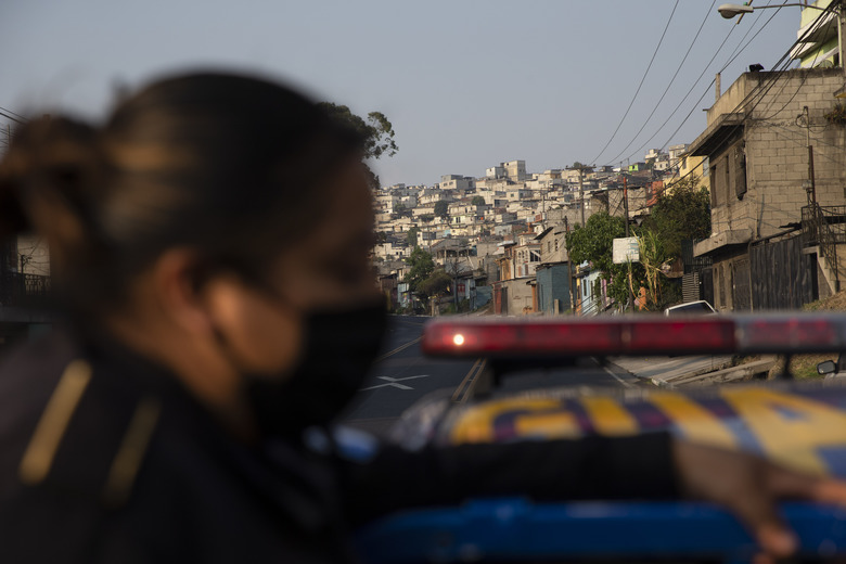 A police officer patrols during the fourth day of a curfew across the country to help prevent the spread of the new coronavirus in Villa Nueva, Guatemala, Wednesday, March 25, 2020. COVID-19 disease causes mild or moderate symptoms for most people, but for some, especially older adults and people with existing health problems, it can cause more severe illness or death. (AP Photo/Moises Castillo)
