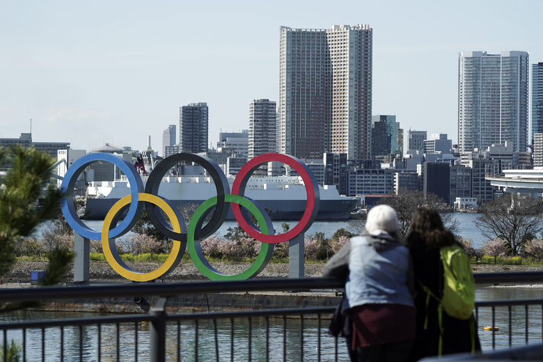 """In this Tuesday, March 3, 2020, photo, tourists look at the Olympic rings, at Tokyo's Odaiba district in Tokyo. Japan's Olympic minister has suggested in Parliament that the Tokyo Olympics might be pushed back a few months from it July 24 opening. The games are under threat from a spreading virus from China that has reached the pandemic stage. But the so-called """"Home City Contract""""signed by the International Olympic Committee and Japanese officials gives the IOC wide latitude in terminating the Olympics. (AP Photo/Eugene Hoshiko)"""