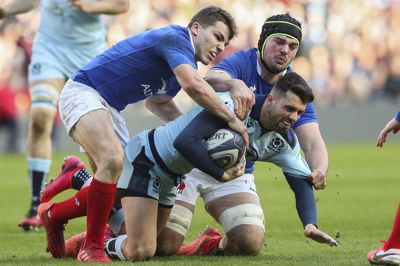 Scotland's Adam Hastings is tackled by France's Antoine Dupont, left, and Gregory Alldritt, top right, during the Six Nations rugby union international match between Scotland and France at the Murrayfield stadium in Edinburgh, Scotland, Sunday, March 8, 2020. (AP Photo/Scott Heppell)
