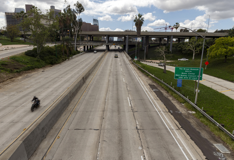 A motorcyclist rides in extremely light traffic along Highway 110 in Los Angeles on Tuesday. California Gov. Gavin Newsom is ordering the state's 40 million residents to stay at home indefinitely.  (AP Photo/Damian Dovarganes)