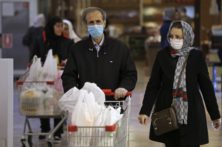 Shoppers wearing face masks and gloves shop at the Palladium Shopping Center, in northern Tehran, Iran, Tuesday, March 3, 2020. Iran's supreme leader put the Islamic Republic's armed forces on alert Tuesday to assist health officials in combating the outbreak of the new coronavirus, the deadliest outside of China. (AP Photo/Vahid Salemi)