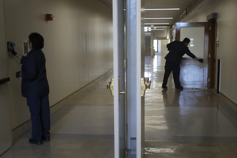 Janitors clean in a hallway in Wheeler Hall on the University of California campus in Berkeley, Calif., Wednesday, March 11, 2020. UC Berkeley has suspended in-person classes due to coronavirus concerns. (AP Photo/Jeff Chiu)