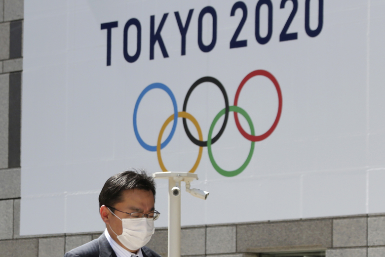 FILE – In this Wednesday, March 25, 2020, file photo, a man walks in front of a Tokyo Olympics logo at the Tokyo metropolitan government headquarters. The postponement of the Tokyo Games has catapulted the sports organizations that make up the backbone of the U.S. Olympic team into crisis. (AP Photo/Koji Sasahara, File)
