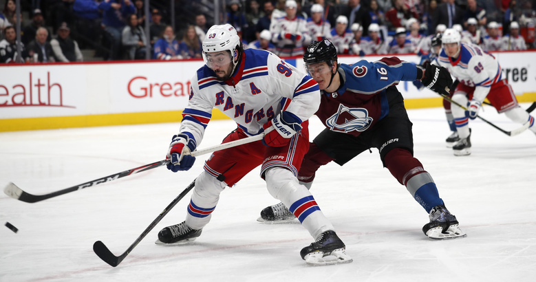 New York Rangers center Mika Zibanejad, left, fires the puck after driving past Colorado Avalanche defenseman Nikita Zadorov during the second period of an NHL hockey game Wednesday, March 11, 2020, in Denver. (AP Photo/David Zalubowski)