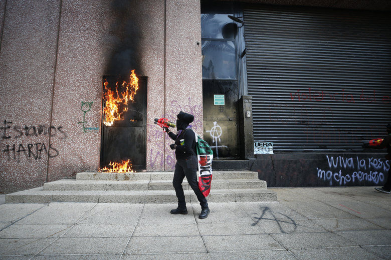 A demonstrator sets fire to the door of a building during a march for International Women's Day in Mexico City, Sunday, March 8, 2020. Protests against gender violence in Mexico have intensified in recent years amid an increase in killings of women and girls.(AP Photo/Rebecca Blackwell)