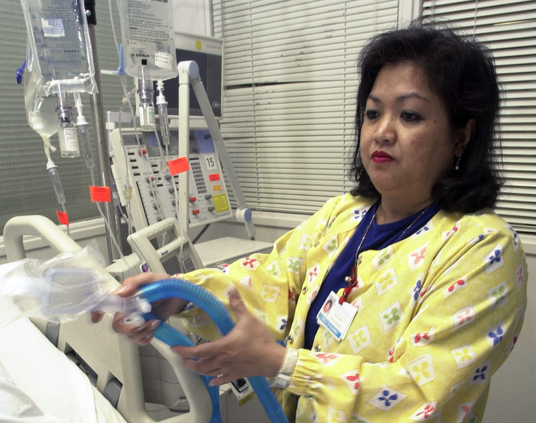 FILE – In this May 25, 2005, file photo, Lovely R. Suanino, a respiratory therapist at Newark Beth Israel Medical Center in Newark, N.J., demonstrates setting up a ventilator in the intensive care unit of the hospital. U.S. hospitals bracing for a possible onslaught of coronavirus patients with pneumonia and other breathing difficulties could face a critical shortage of mechanical ventilators and health care workers to operate them. (AP Photo/Mike Derer, File)