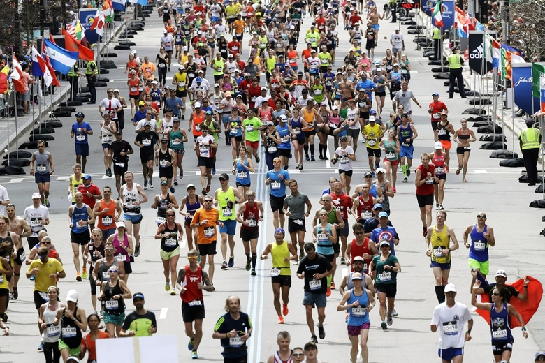 FILE – In this April 17, 2017, runners  in the 121st Boston Marathon head down the stretch to the finish line in Boston. The 124th Boston Marathon is scheduled for Monday, April 20, 2020. Boston Marathon organizers say they're postponing the prestigious race until Sept. 14 because of concerns over the coronavirus pandemic. (AP Photo/Charles Krupa, File)