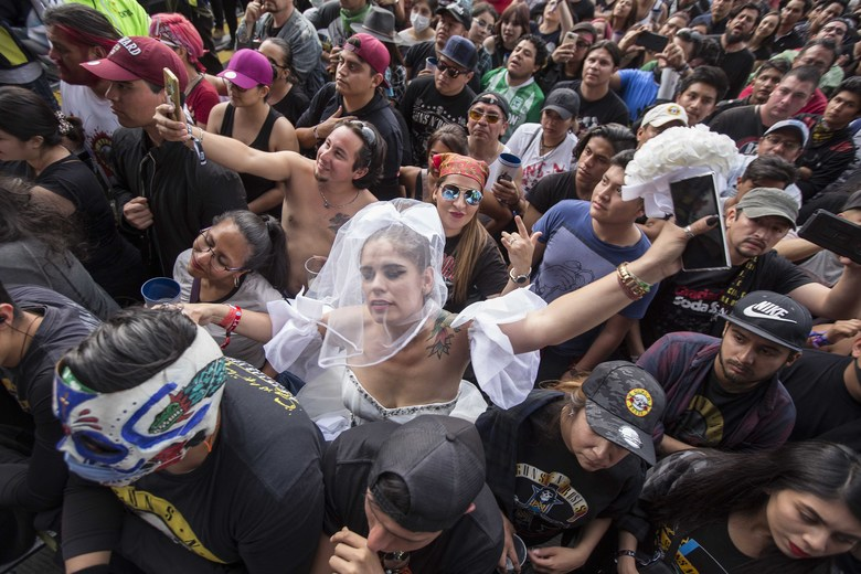 A woman dressed as a bride dances at the Vive Latino festival in Mexico City, Saturday, March 14, 2020. On Friday afternoon organizers confirmed that the 21st edition of the festival will go on as planned.  (AP Photo/Christian Palma)