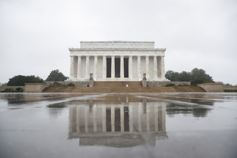 The Lincoln Memorial is seen on a rainy morning in Washington, Monday, March 23, 2020, as only a few National Park Police can be seen on the steps. As Washington continues to work to mitigate the spread of the coronavirus (COVID-19), Mayor Muriel Bowser extended road closures and other measures to restrict access to the Tidal Basin, the the cherry blossoms, and other tourist attractions. (AP Photo/Carolyn Kaster)