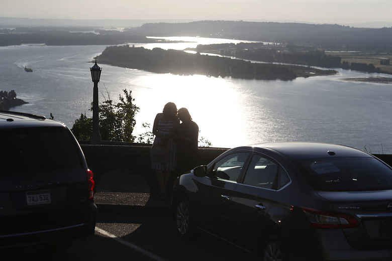 In this July 22, 2019, photograph, a couple look over the Columbia River as the suns sets from the Vista House at Crown Point State Park near Corbett, Or. People are headed out into the great outdoors as the new coronavirus has made for turbulent times. The new coronavirus causes mild or moderate symptoms for most people, but for some, especially older adults and people with exisitng health problems, it can cause more severe illness or death. (AP Photo/David Zalubowski)