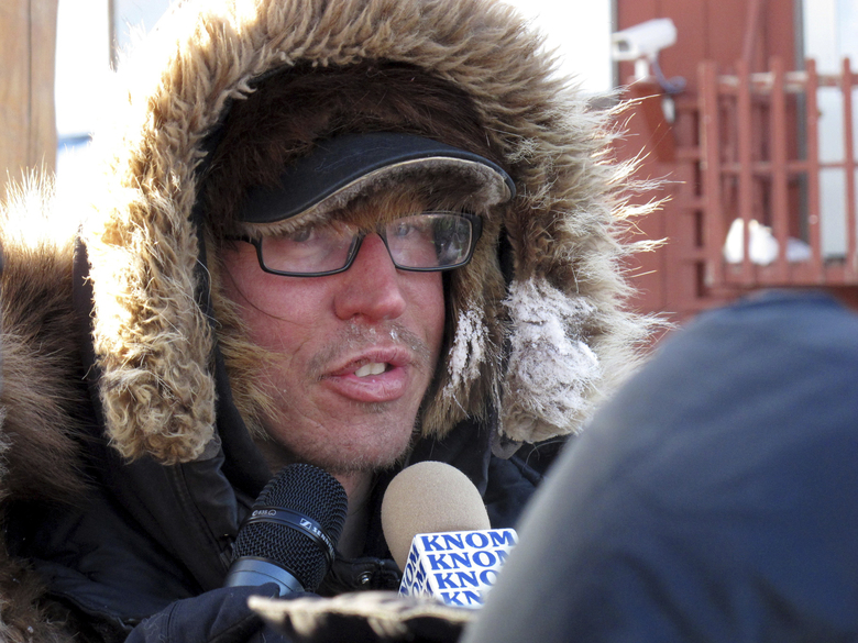 FILE – In this March 12, 2012 file photo, musher Brent Sass speaks to reporters after completing the nearly 1,000 mile Iditarod Trail Sled Dog Race in Nome, Alaska. Sass, coming off back-to-back wins in another long-distance sled dog race, was the first to reach the halfway point of this year's Iditarod Trail Sled Dog Race. The native of Minnesota living near the Alaska community of Eureka arrived late Wednesday night, March 11, 2020 with 13 dogs in harness at the checkpoint in Cripple, where Sass said he planned to take his mandatory 24-hour rest period. (AP Photo/Mark Thiessen, File)