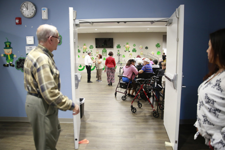 Seniors gather in an auditorium at Little Havana Activities and Nutrition Centers in Miami. The new coronavirus is posing a special challenge for nursing homes and other facilities that provide care for the elderly. (AP Photo/Brynn Anderson, file)