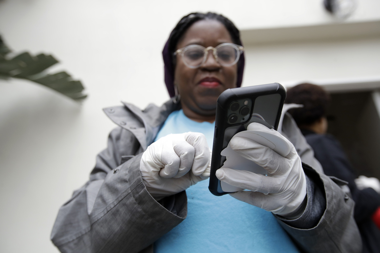 Millie Phaeton wears gloves as she checks her cell phone while volunteering at a food distribution center set up by the Dream Center Monday, March 16, 2020, in Los Angeles. (AP Photo/Marcio Jose Sanchez)