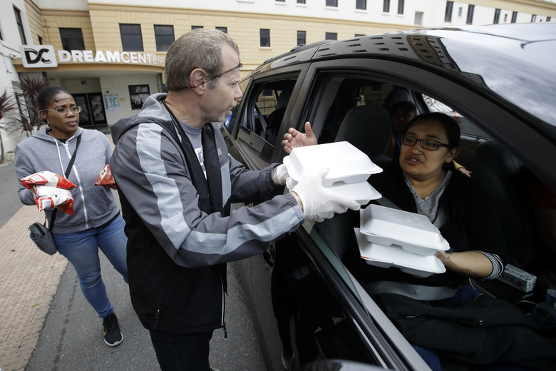 Kenny Hultquist, center, hands out lunches to Melissa Polanco, right, at a food distribution center set up by the Dream Center for those in need due to the coronavirus outbreak, Monday, March 16, 2020, in Los Angeles. (AP Photo/Marcio Jose Sanchez)