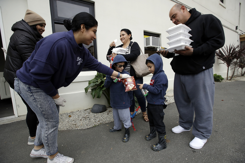 Volunteer, Pahola Campos, second from left, hands out lunches to the Garcia family, mom Marie, top center, dad Sergio, at right, David, bottom center in glasses, and Daniel at a food distribution center set up by the Dream Center for those in need due to the coronavirus outbreak, Monday, March 16, 2020, in Los Angeles. (AP Photo/Marcio Jose Sanchez)