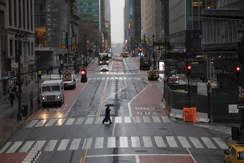 FILE – In this March 23, 2020, file photo, a commuter crosses 42nd Street in front of Grand Central Terminal during morning rush hour, in New York. (AP Photo/Mark Lennihan, File)