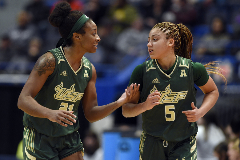 South Florida's Shae Leverett, left, talks with Elena Tsineke, right, after Tsineke fouled in the first half of an NCAA college basketball game against Connecticut, Monday, March 2, 2020, in Hartford, Conn. (AP Photo/Jessica Hill)