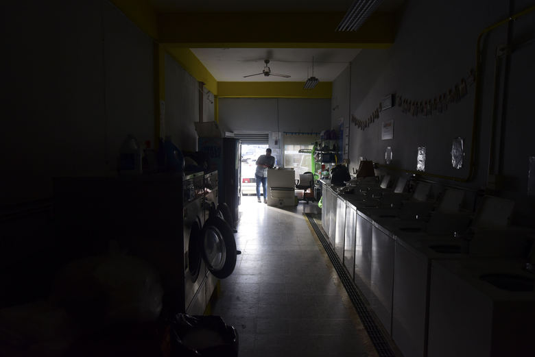 Laundromat owner Jesus Vazquez pauses before closing his shop to comply with the government's curfew aimed at curbing the spread of the new coronavirus, which is shuttering all non-essential businesses for two weeks in San Juan, Puerto Rico, Friday, March 20, 2020. (AP Photo/Carlos Giusti)