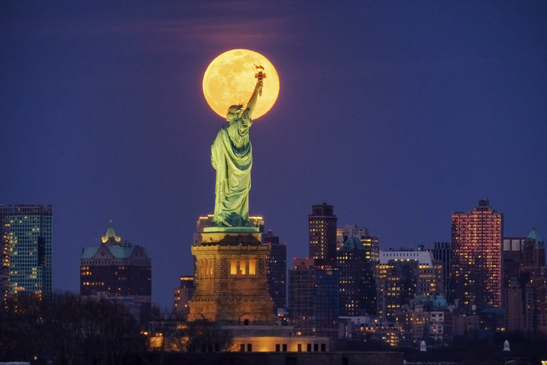 The rising full moon shines behind the Statue of Liberty, Monday evening, March 9, 2020, in New York City. (AP Photo/J. David Ake)